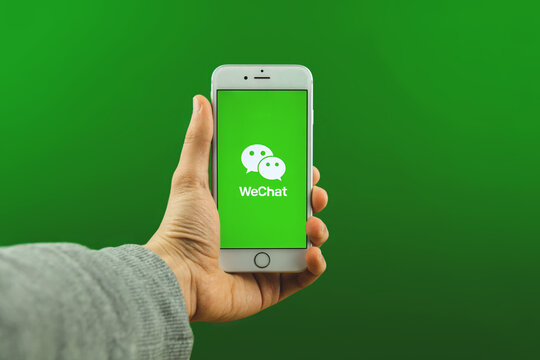 Kharkov, Ukraine - February 25, 2021: Man holds Apple iPhone smartphone with WeChat app on it, chinese social network logo on green background