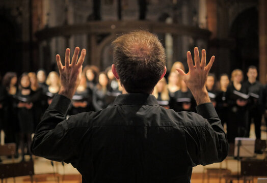 Musician leads a choir during a concert in a cathedral. Musical rehearsals before the concert during the Christmas period. Life of musicians and classic holy music.