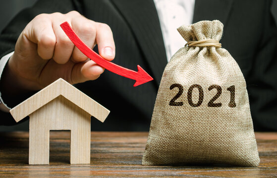 A businessman holds an arrow down near the house and a 2021 money bag. Forecasting the real estate market. Interest rates. Mortgage, loan. Investment, profit and income. Decline in housing prices