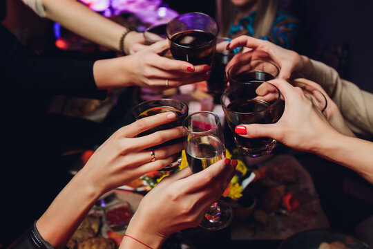 Clinking glasses with alcohol and toasting, party.