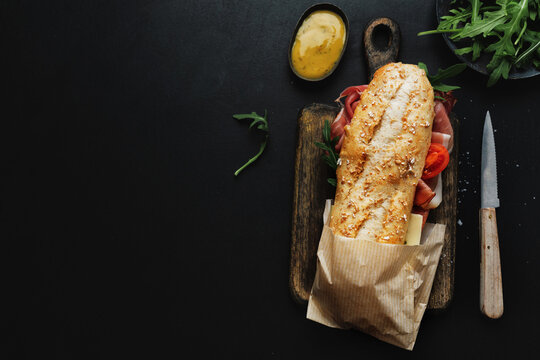 Tasty sandwich with meat on dark background