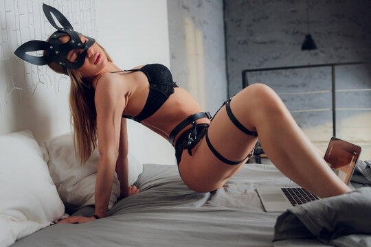 Beautiful, young girl posing in front of a web camera, working as a model.