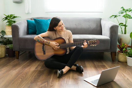 Hispanic woman practicing a new song on the guitar
