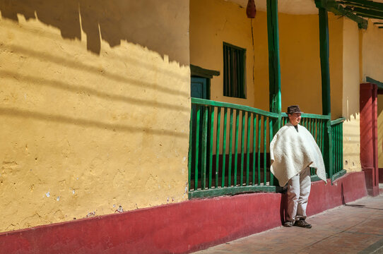 Farmer rests next to an old colonial house in the main park of Sora in Boyacá, Colombia