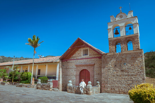 Facade of the church of Sora, Boyacá, Colombia on a beautiful sunny day. Man wearing the typical Boyacá ruana rests there.