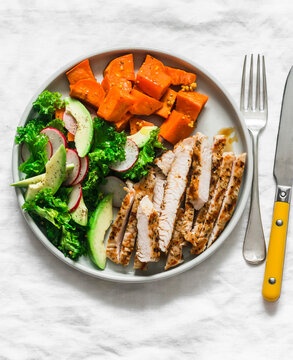 Balanced diet lunch - grilled turkey, boiled sweet potatoes, kale cabbage, avocado, cucumbers, radish salad on a light background, top view