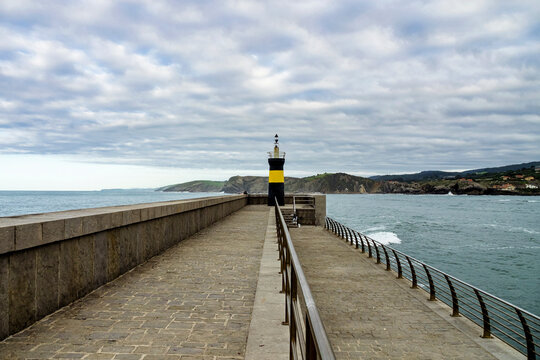 view of the dike and the ligthouse at comillas, cantabria spain