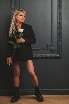 Portrait photo cute middle aged 45 years old blonde woman in domestic room with rose. Female in style clothes in interior background. Concept dating service. Indoors positive confident mature woman
