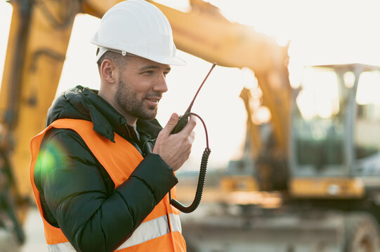 Young engineer talking radio communication (walkie talkie) and wearing a white helmet and construction orange vest. Close up engineers working on a building site with the sunny background.