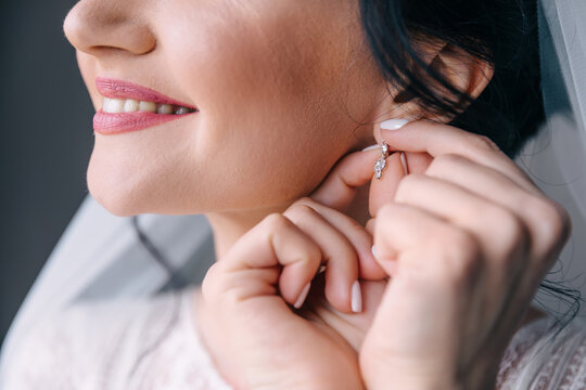 A beautiful bride in a white robe with curly hair smiles and straightens an earring on her ear. Wedding portrait.