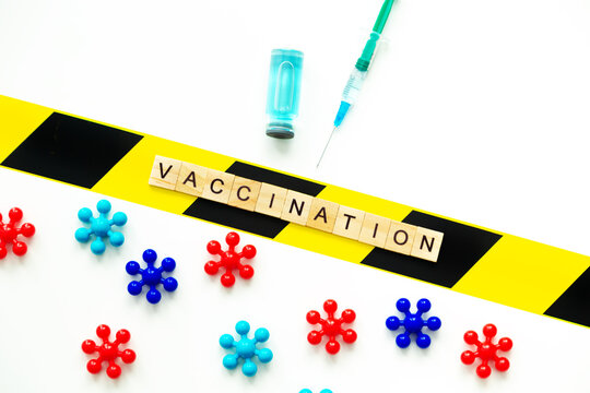 """Wooden letters form the inscription """"Vaccination"""". Vial with vaccine, syringe and microbes on a white background."""
