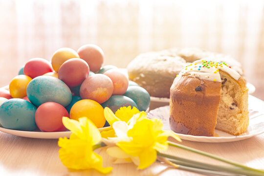 Sliced Easter orthodox sweet bread, kulich, colored eggs and a bouquet of daffodils.