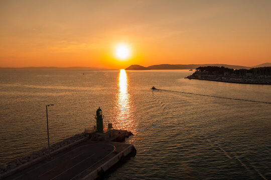 Sunset over the Adriatic Sea and its boats playing in the reflections at the entrance to the port of Split in Croatia