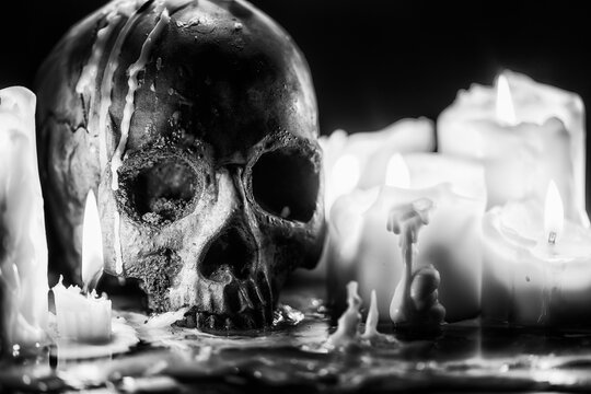 Candles and human skull in darkness closeup in black and whiter