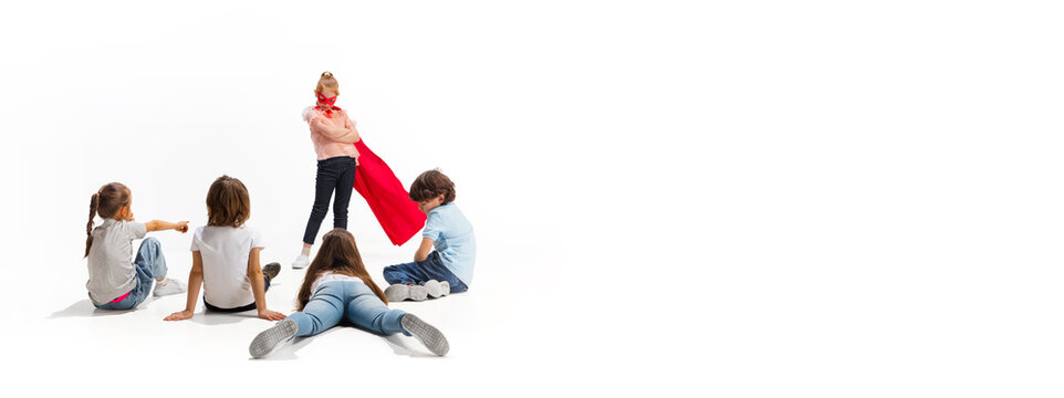 Flyer. Child pretending to be a superhero with her friends sitting around her. Kids excited, inspired by their strong, brave friend in red coat isolated on white background. Dreams, emotions concept.