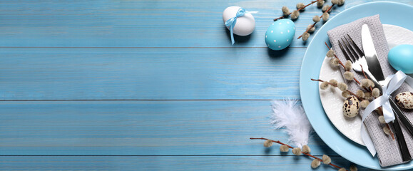 Festive Easter table setting with eggs on light blue wooden background, flat lay. Space for text