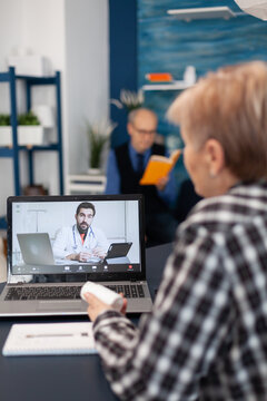 Sick senior woman talking with young doctor during remote consultation. Elderly telemedicine online conference call with practitioner doctor using modern healthcare technology, web diagnosis