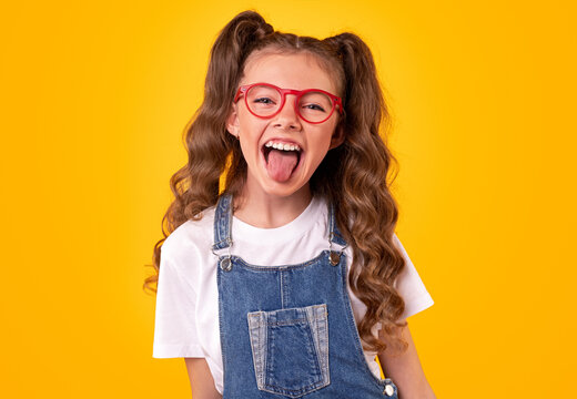 Funny girl in glasses showing tongue