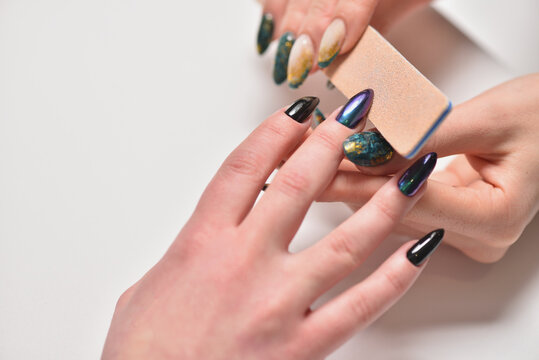 Manicurist files the client's nails with a nail file, close up