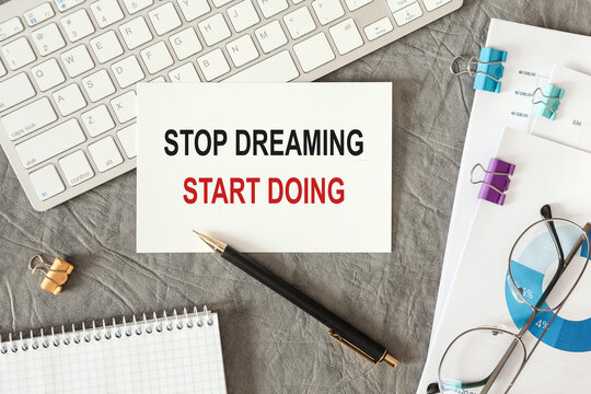 Stop Dreaming Start Doing is written in a document on the office desk