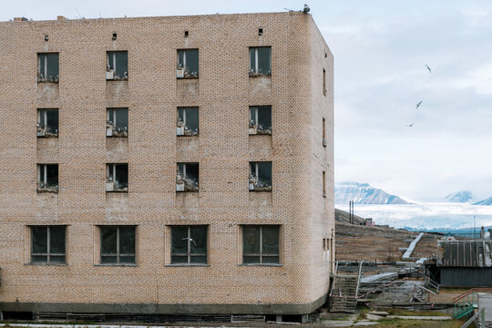 Ruined building with mountain in the background in the Ghost Town of Pyramiden, Svalbard