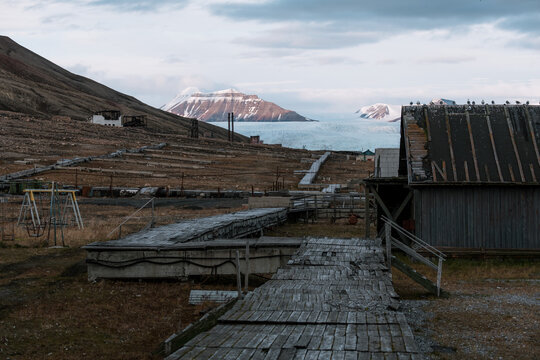 Ruined building and walkway with mountain and glacier in the background in the Ghost Town of Pyramiden, Svalbard during sunset