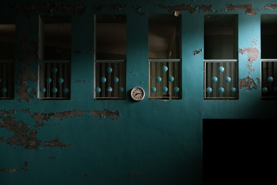 Abandoned gym with blue wall and broken clock in the Ghost Town of Pyramiden, Svalbard