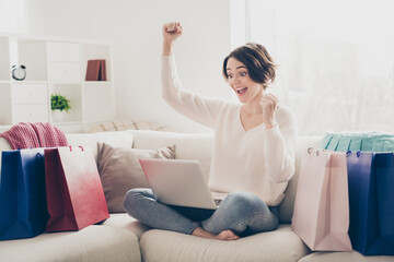 Full body photo of bob haired young woman raise fists winner look hold laptop sit couch shopping bags indoors in living-room Wall mural