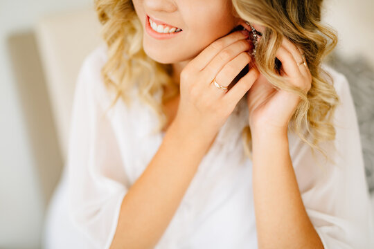 Bride wearing white peignoir puts on an earring and smiling while preparing for the wedding