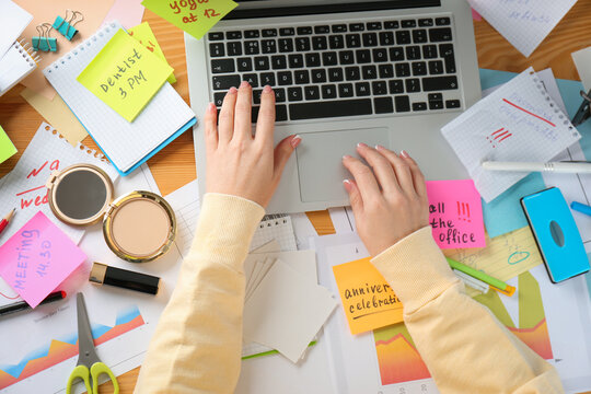 Woman using laptop at messy table, top view. Concept of being overwhelmed by work