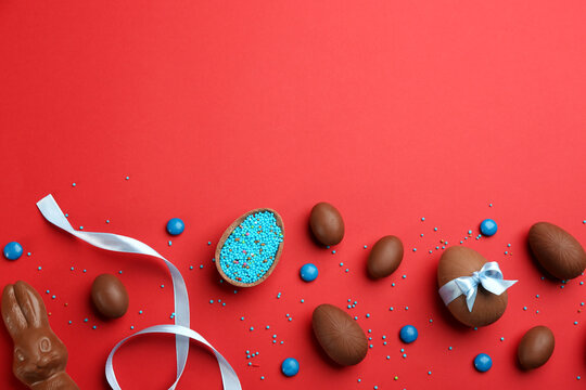 Sweet chocolate eggs and candies on red background, flat lay. Space for text