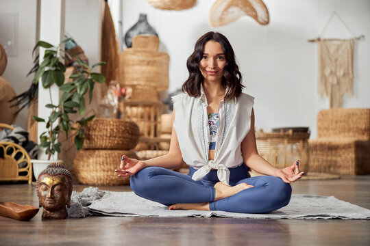 Mature woman is doing yoga and meditative practics in bali style decorated room