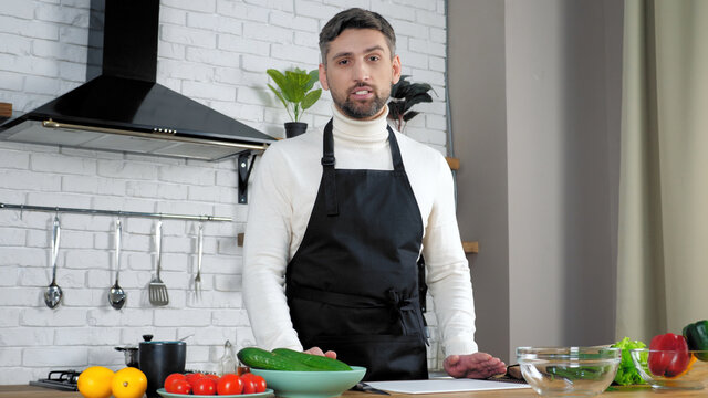Man professional chef in black apron looks camera tells teaches housewife student, online video call conference chat webcam view laptop computer in home kitchen, remote master class culinary course