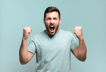young handsome adult man shouting aggressively with an angry expression or with fists clenched celebrating success