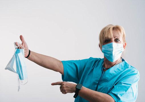 enfermera con varias máscaras protectoras colgando de la mano y con la mano hacia adelante marcando la distancia social
