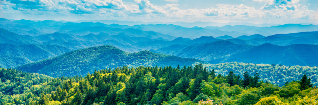 A panoramic view of the Smoky Mountains from the Blue Ridge Parkway in North Carolina. Blue sky with  clouds over layers of green hills and  mountains. North Carolina. Image for banner and web header.