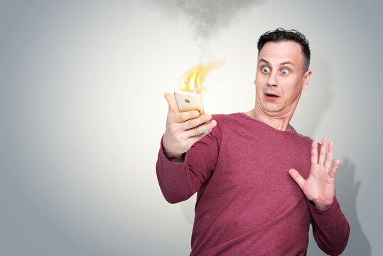 Frightened and surprised man with smartphone on fire in his hand. The situation with fire phone batteries.