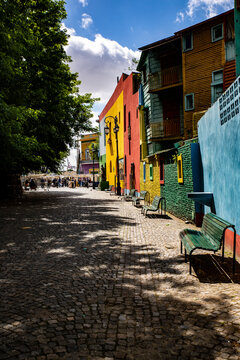 Argentina, Buenos Aires, La Boca. Painted building houses and cobblestone street.