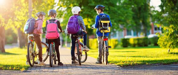 Children with rucksacks riding on bikes in the park near school