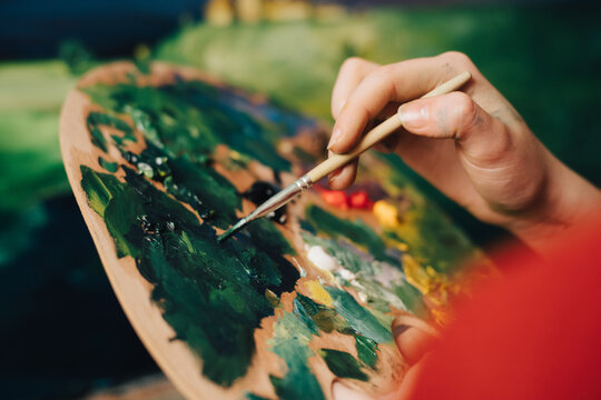 woman artist paints a picture with oil paints on canvas and palette in hand