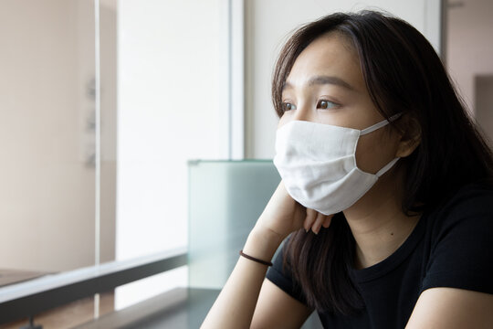 young Asian woman properly wearing face mask in working office, concept of taking precaution measure, social distancing, new normal lifestyle while waiting for coronavirus cure, COVID-19 vaccine.
