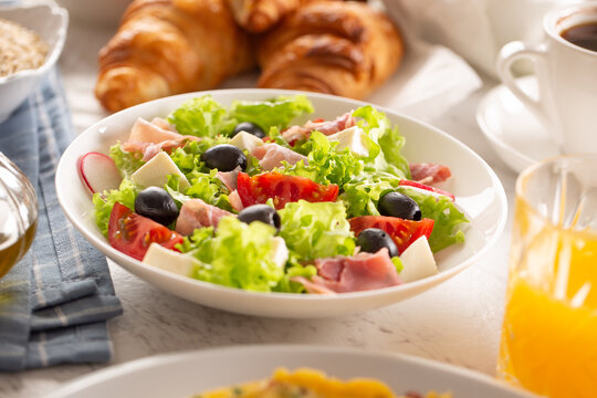 Healthy salad in a bowl with olives, raddishes, tomato, cheese and lean ham served for breakfast