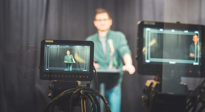 Young journalist in a television recording studio is talking into a microphone, blurry film cameras