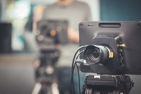 Professional film camera on tripod, broadcasting studio, spotlights and other recording equipment