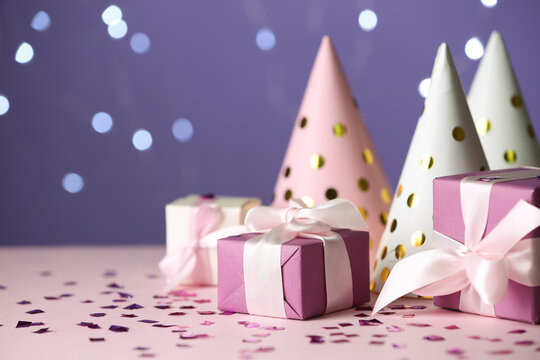 Gift boxes and party hats on pink table against blurred lights. Space for text