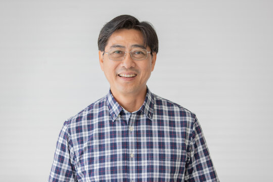 Portrait close up shot of middle aged asian male model with short black hair wearing blue plaid shirt with stand smiling in front of white background