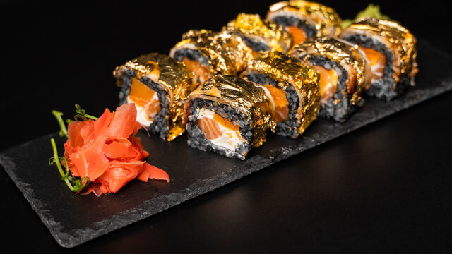Custom sushi roll with nori, cuttlefish ink, fresh salmon, cream cheese, pepper pumpkin, eel, unagi sauce and edible gold leaf with red ginger, wasabi on a square plate on black table and background.