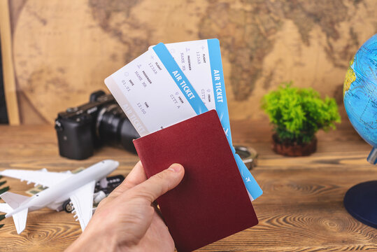 Hand is holding a passport and plane tickets over a wooden table with travel supplies. Vacation and booking concept