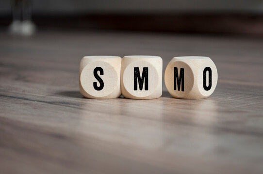 Cubes, dice or blocks with acronym smo Social Media Optimization and smm Social Media Marketing on wooden background