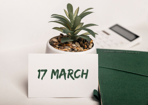 17 March inscription on office desk with plant and green notebook